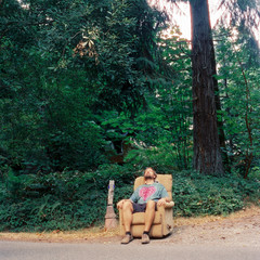 Bearded man in shorts and tie-dyed t-shirt relaxes in an easy chair on the side of a road.