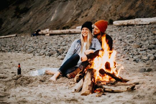 couple enjoying campfire at the beach