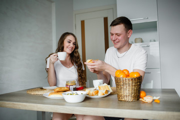 lovers having breakfast together in the kitchen in the morning