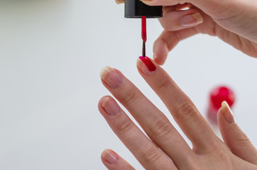 Photograph of a girl painting her nails.