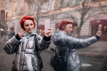 Funny girl taking selfie near the wall  reflecting GUM Moscow
