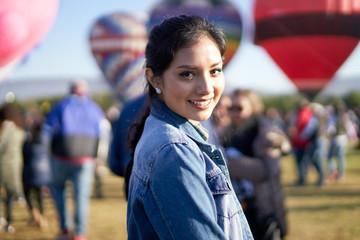Young woman looking at camera, at a balloon festival