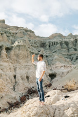 Portrait of young male in eastern oregon landscape canyon blocking sun with shade of hand