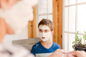 big sister putting trips of plaster on little boy to make mask
