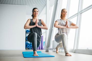 Two female friends doing yoga in a bright studio.