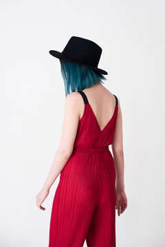 Back of young woman with blue hair wearing red jumpsuit