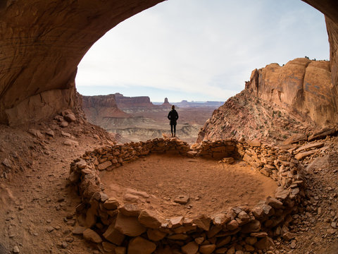 Young woman exploring an ancient Native American archeological ruin in Utah.