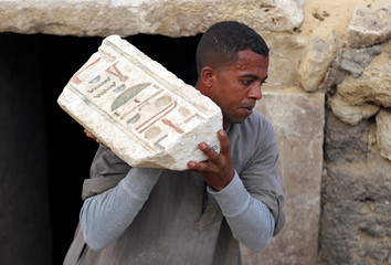 A worker carries an artefact outside the tomb of Khufu-Imhat, at the Saqqara area near its necropolis, in Giza