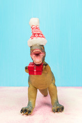 Cute dinosaur with Santa hat holding Christmas gift. Falling snow.
