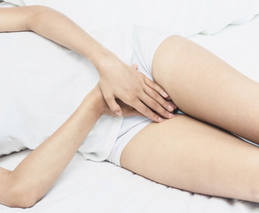 Beautiful Attractive Asian woman wearing white shirt sitting on bed have a bladder pain or uti pain after wake up in the morning feeling so illness,Healthcare Concept