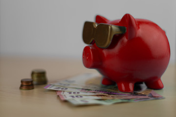 cool red piggy bank with golden glasses with euro coins and note isolated on wooden table