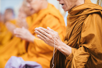 Close up of Thai monk praying focus at hand with white rope.