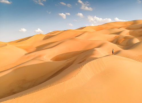 person in Liwa desert, part of Empty Quarter, the largest continuous sand desert in the world