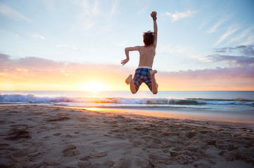 Boy leaping high in the air at the beach at sunset