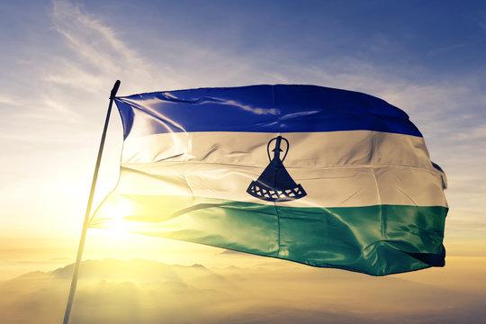 Lesotho Mosotho Basotho flag textile cloth fabric waving on the top sunrise mist fog