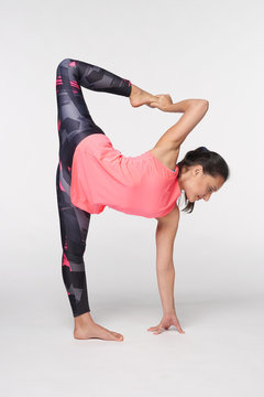 Woman practicing yoga Ardha Chandrasana over white