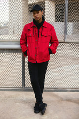 Portrait of cool latin man wearing a red jacket standing on the street.