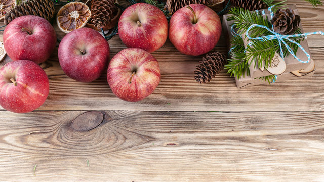 Web banner Christmas background. Red apples, gifts, fir branches and cones on a wooden background