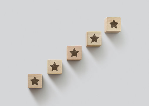 Wooden blocks arranged in stair shape with the five star symbol. The best rating, the best ranking, the best service, goal, success concept.