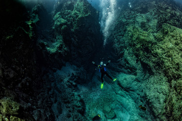 Scuba diver underwater in the deep blye ocean abyss