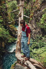 Young Man Standing on the Narrow Bark of a Interesting Tree Above a Rushing Stream