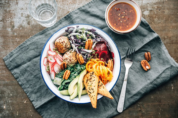 Food: healthy raw salad with quinoa balls and marinaded, fried t