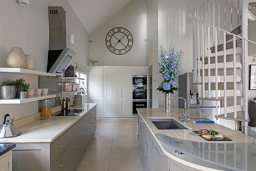 Modern kitchen area with spiral staircase leading to next level.