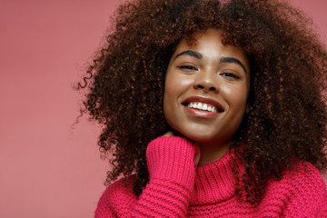 Portrait of a young African American afro woman in pink studio smiling touching her chin