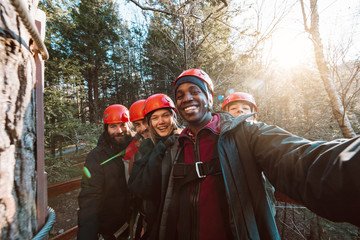 A group of friends take a selfie before starting their outdoor zip line adventure