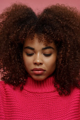 Portrait of a young African American afro woman in pink studio with eyes closed
