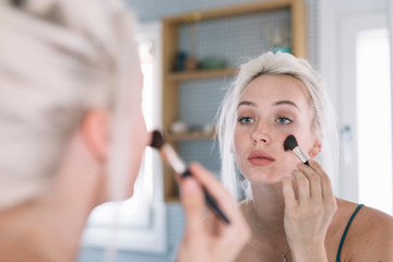 Young model applying makeup