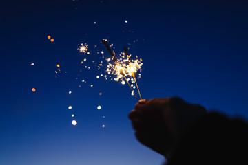 Female hand holding sparkler against a dark sky