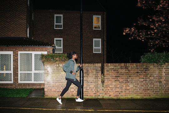 Ethnic woman running at night