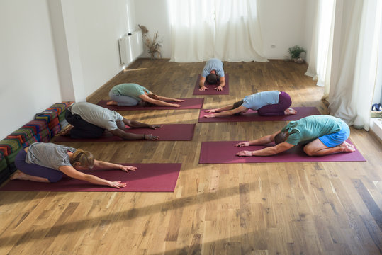 People standing in yogic child's pose