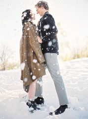 A young couple cuddling in the morning light in winter forest and snow falling from above