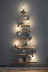 Minimal handmade Christmas tree illuminated with yellow light bulbs