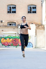 Running young woman on urban background