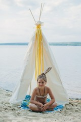 Lovely little girl with feathers in her hair sitting by teepee house