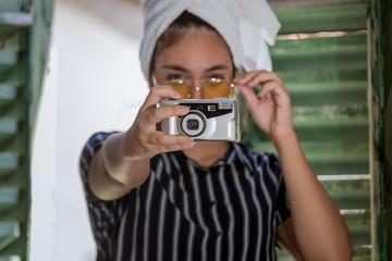Chica joven con cámara de fotos analógica antigua y gafas amarillas posando en la ventana de madera