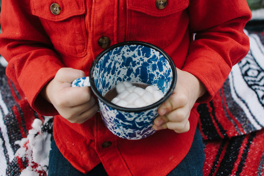 child holds cup of hot chocolate and marshmallows
