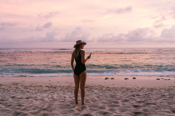 young woman in a swimsuit is standing on the ocean coast looking into the distance with the phone in hands