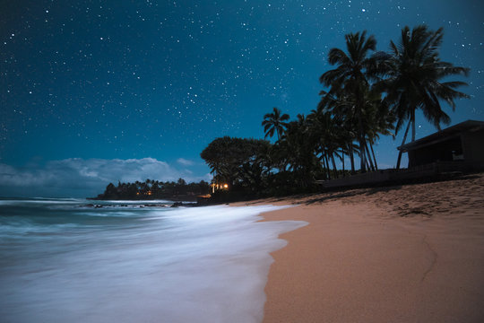 Beautiful Tropical Island Paradise Scenic View with Starry Night Sky with Palm Tree Silhouette with Tranquil Colorful Blue Ocean Water Coming on Sandy Beach in Maui Hawaii