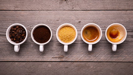 Foto op Canvas koffiebar top view of a sequence of cups with coffee beans and ground coffee, sugar cane, and expressed