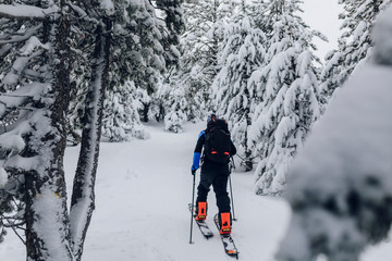 Young man moving up the snowy mountain with a splitboard