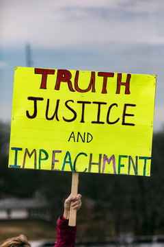 Protest: Person Holds Up Sign Calling For Impeachment