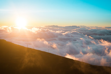 Beautiful Colorful Sunrise Sky at Dawn from the Top of Haleakala Volcano in Maui Hawaii High on Mountain Top with Sun Rays Through the Clouds of Amazing Landscape in Island Paradise