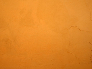 bright rough textured orange paint with cracks on a plastered concrete wall