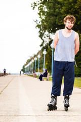 Active young man rollerskating outdoor.