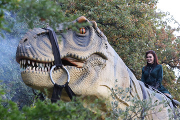 A cosplayer sits on a life-size model of a dinosaur during an exhibition at the Nikitsky Botanical Garden outside Yalta