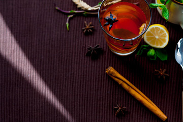 Oriental tea on a brown cloth Mat with spices and lemon. Lemon, mint, ginger, cinnamon.